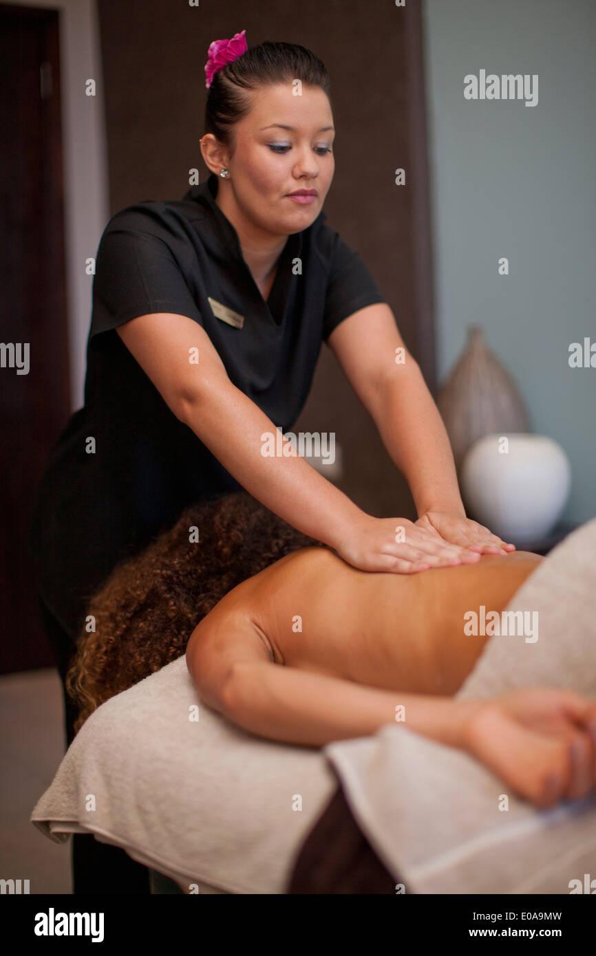Mujer joven tumbado en la parte delantera con un masaje en el spa Foto de stock