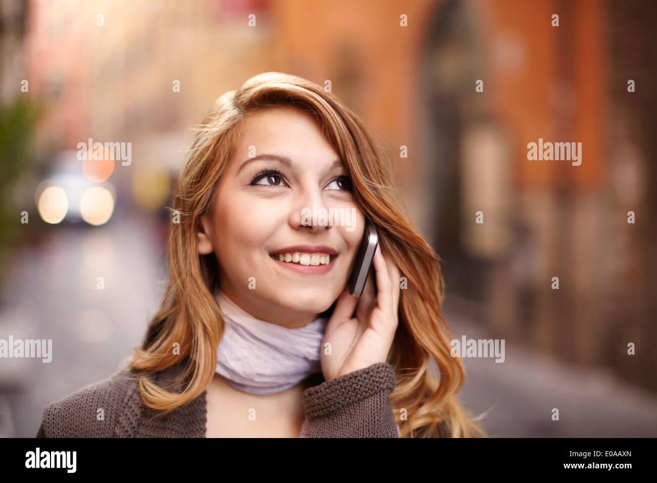 Mujer joven chateando en el smartphone en la calle Roma, Italia Imagen De Stock