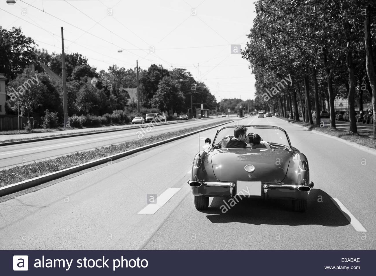 B&W imagen sólo de pareja besándose en coche por la autopista Imagen De Stock
