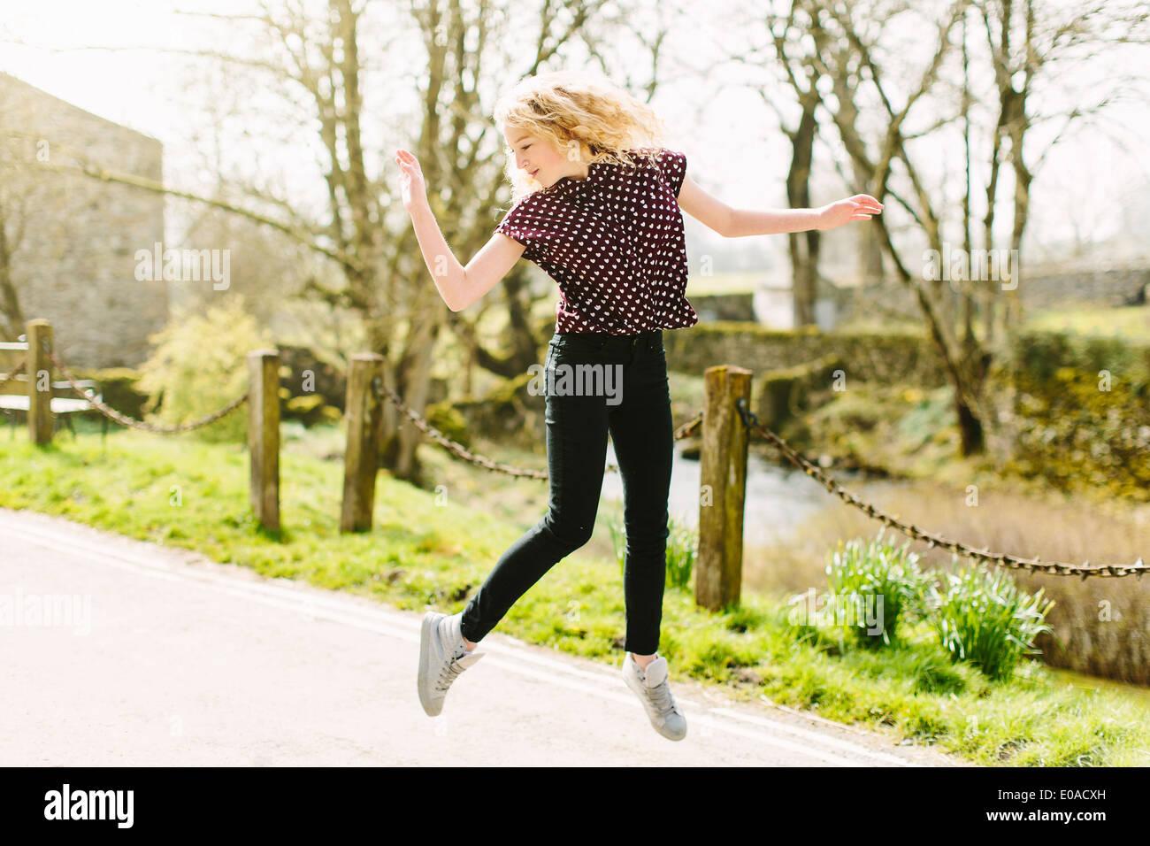 Adolescente Saltando sobre caminos rurales de aire. Foto de stock