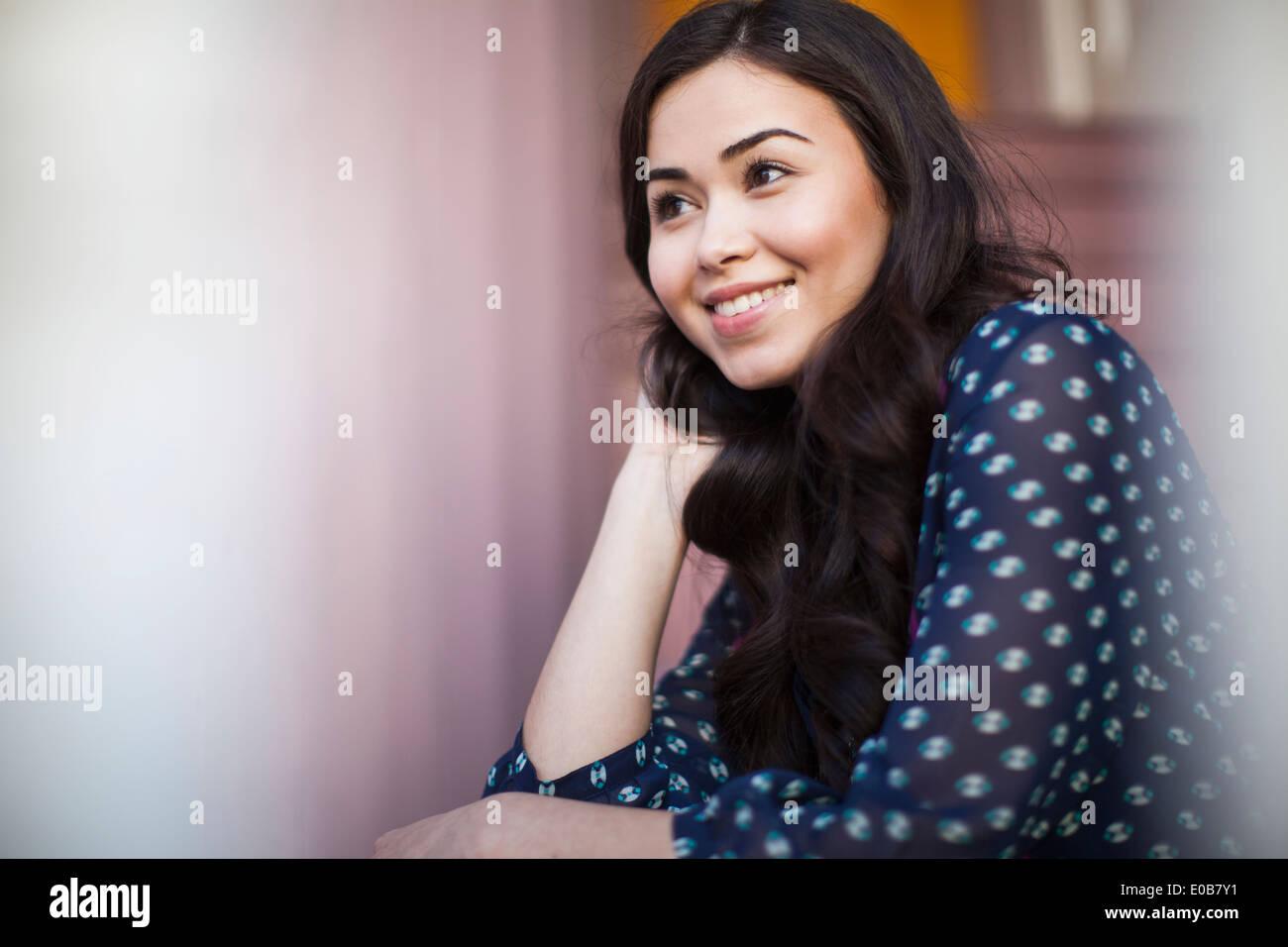 Mujer joven sonriente y mirando a otro lado Imagen De Stock