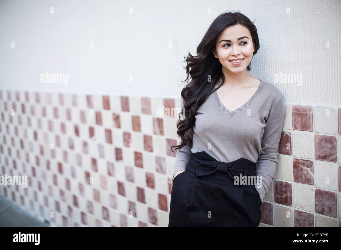 Retrato de mujer joven, apoyado contra la pared de azulejos Imagen De Stock