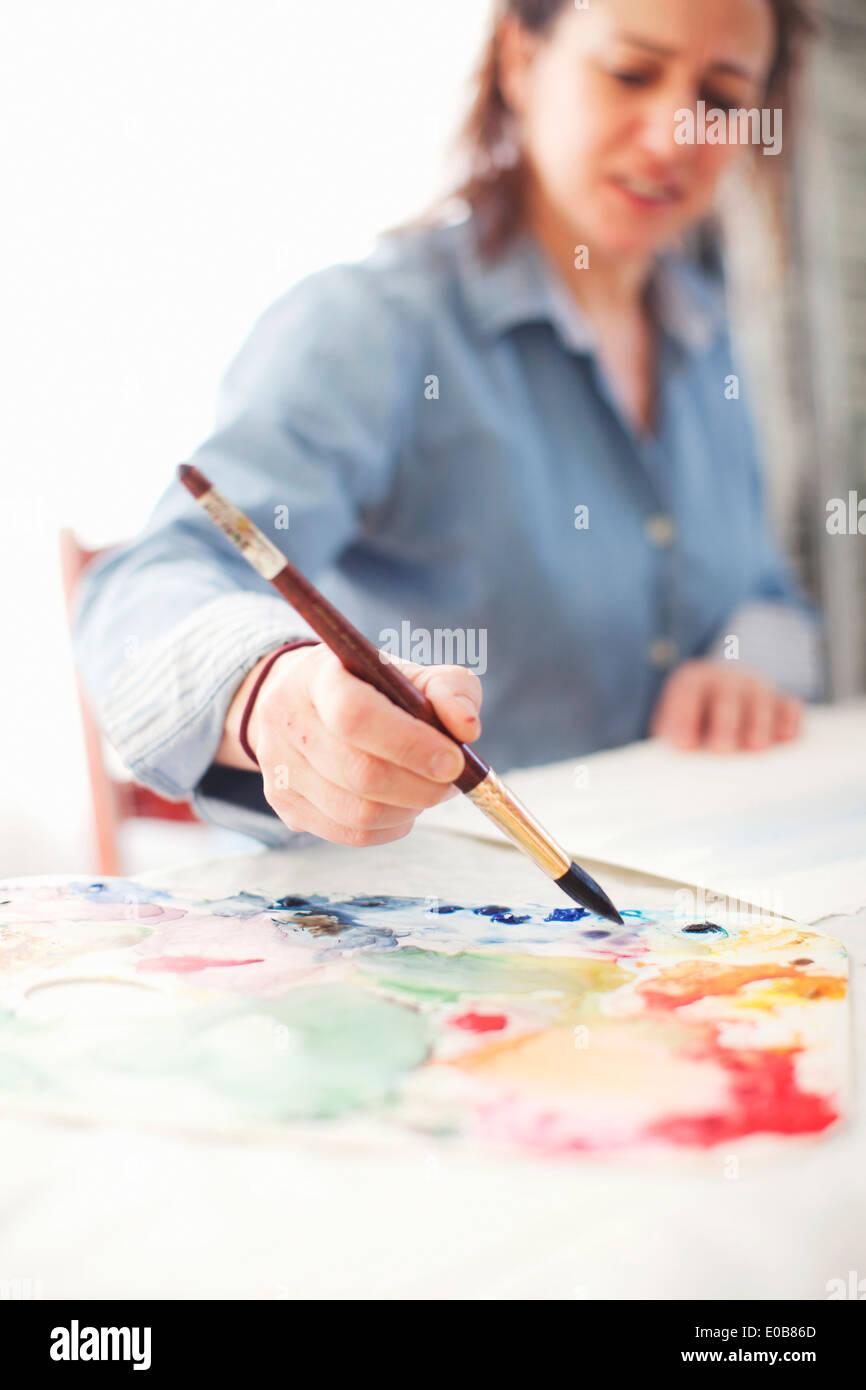Mujer madura artista pintura acuarela en studio Imagen De Stock