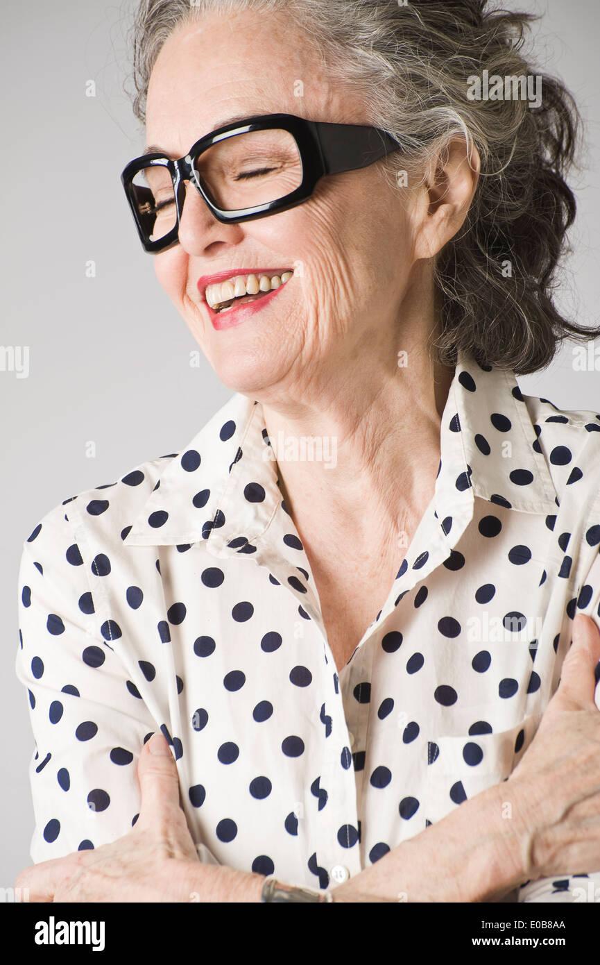 Retrato de mujer mayor, con los brazos cruzados, riendo Imagen De Stock