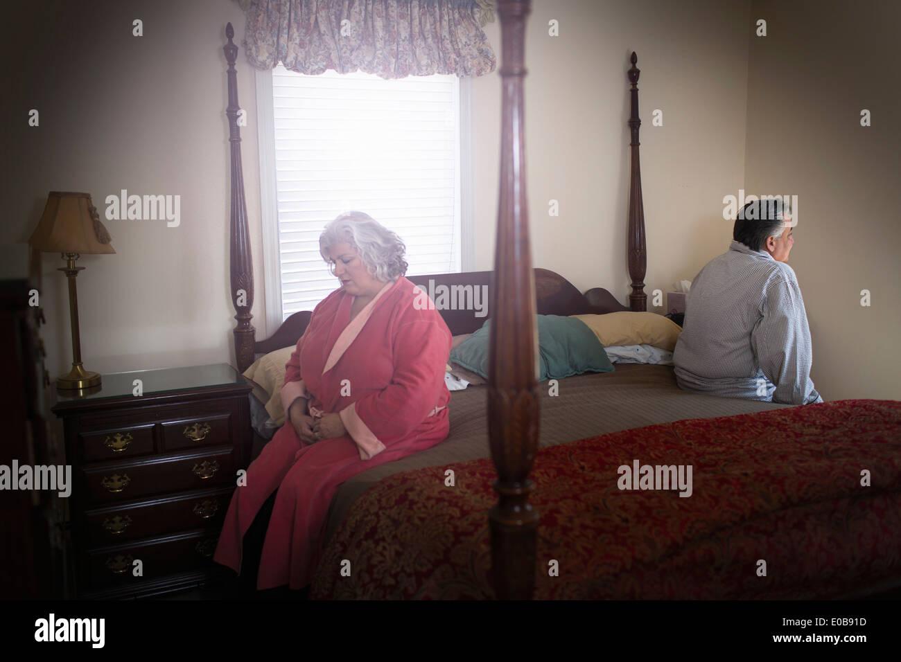 Pareja sentados en lados opuestos de la cama Foto de stock