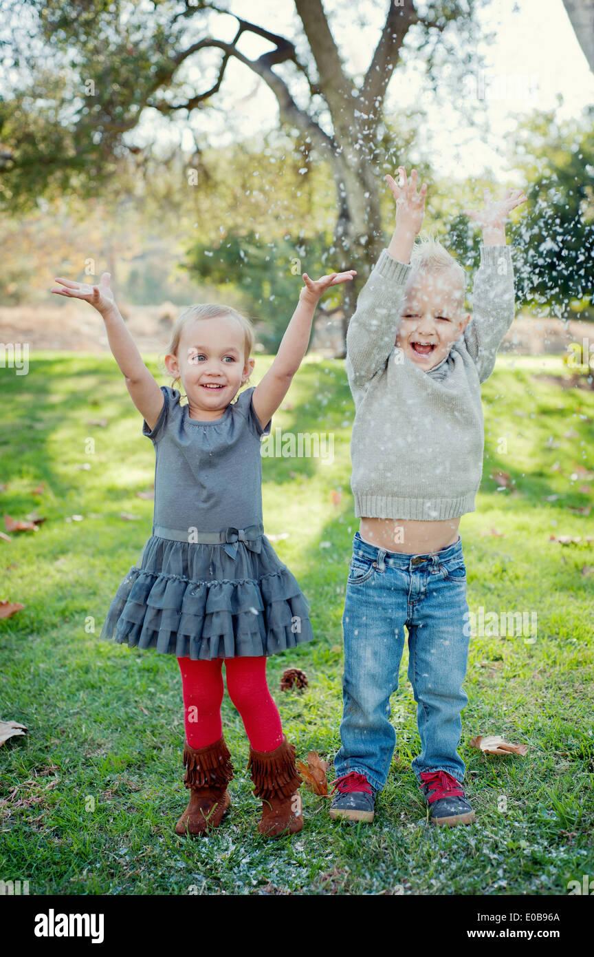 Hermano y hermana con los brazos levantados, en el jardín Imagen De Stock