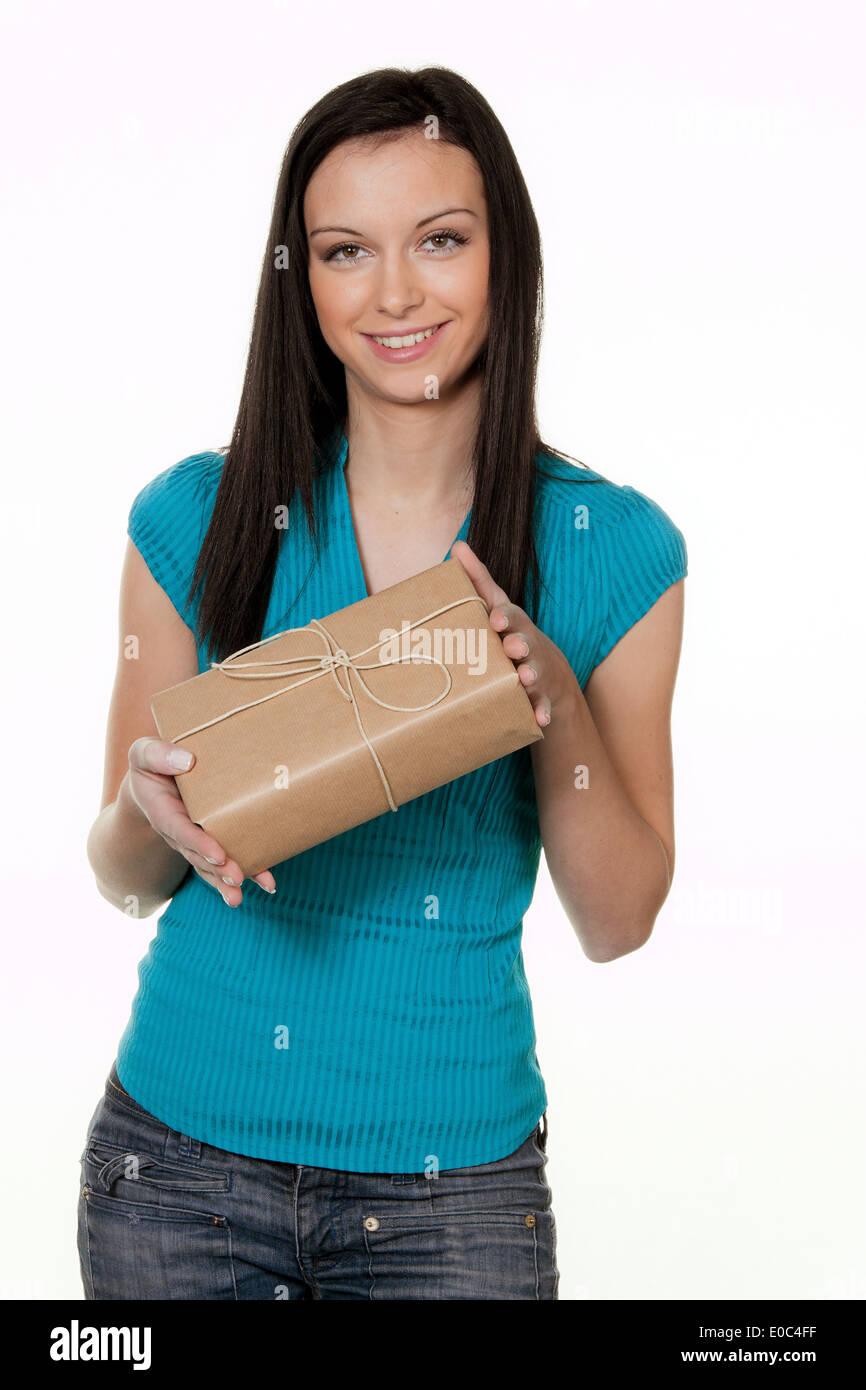 Mujer con paquete de un servicio de despacho. Antes Hijntergrund blanco, Frau mit Paket eines Versanddienstes. Vor weissem Hijntergr Foto de stock