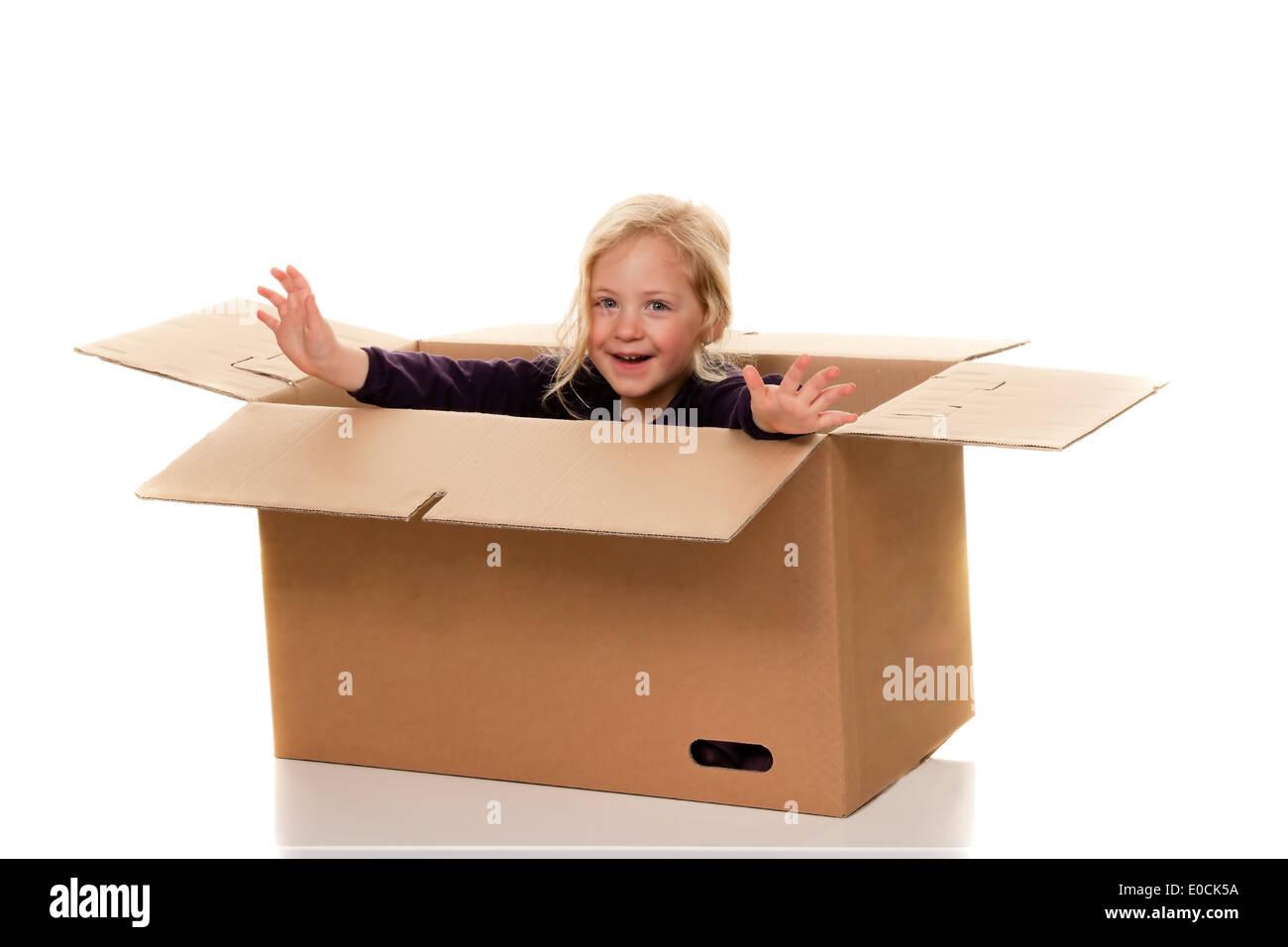 Niño en mover el cartón. Se encuentra con el movimiento en la caja., especie en Umzugskarton. Liegt beim Umzug en Schachtel. Foto de stock