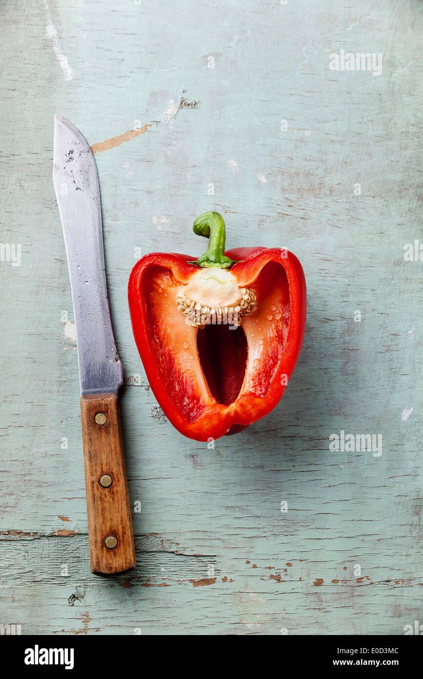 La mitad del pimiento rojo y el cuchillo en la textura de fondo azul Foto de stock