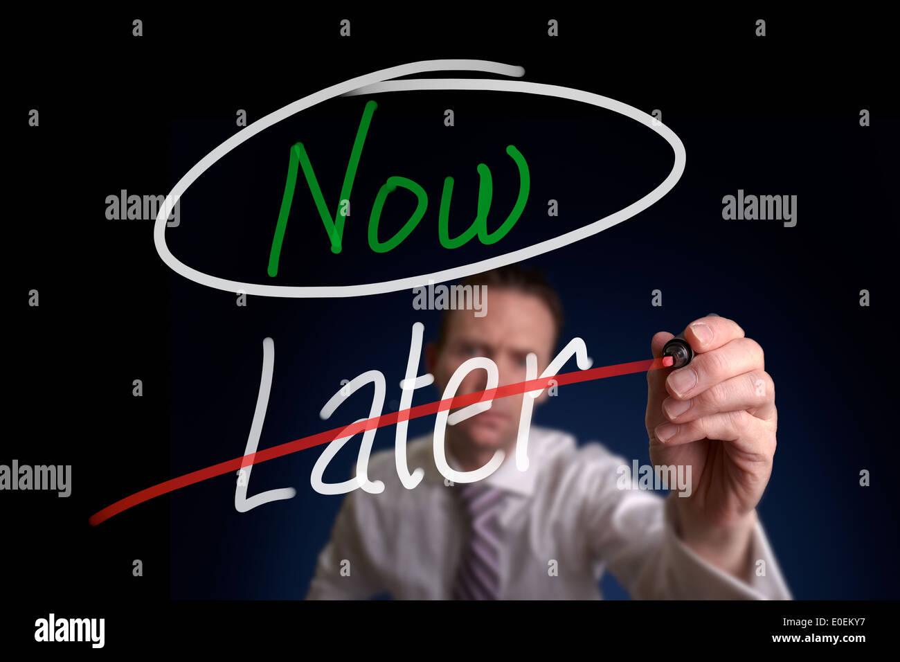 Un empresario escribir, eligiendo ahora en lugar de más tarde, concepto. Imagen De Stock