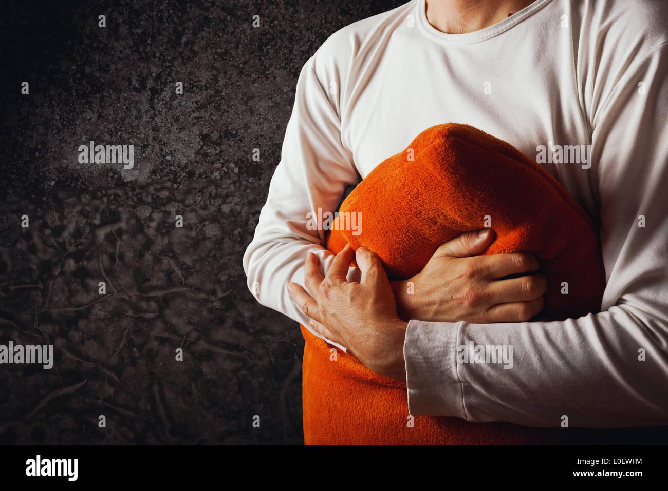 Hombre abrace almohada naranja en una habitación oscura. Concepto de duelo, tristeza y depresión. Imagen De Stock