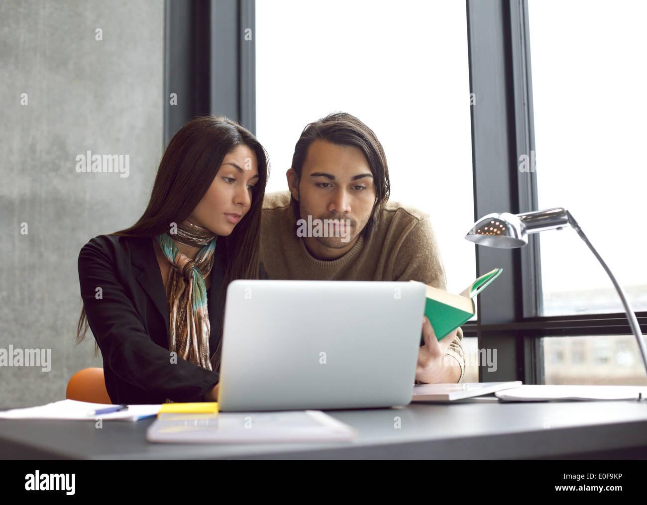 Jóvenes universitarios, la búsqueda de información en libros y laptop para sus estudios. Sentado a la mesa estudiando juntos. Imagen De Stock