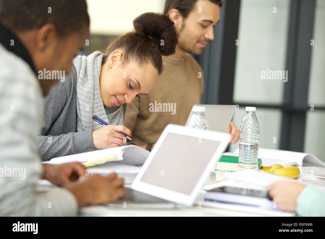 Joven afroamericana tomando notas de libros para su estudio. Estudiantes sentados a la mesa con libros y laptop estudiando. Foto de stock