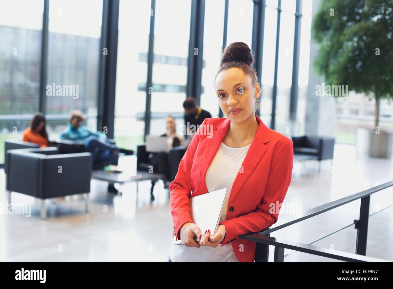 Seguro joven afro americana mujer sosteniendo un portátil por una verja de pie mirando a la cámara. Joven Empresaria en la oficina. Imagen De Stock