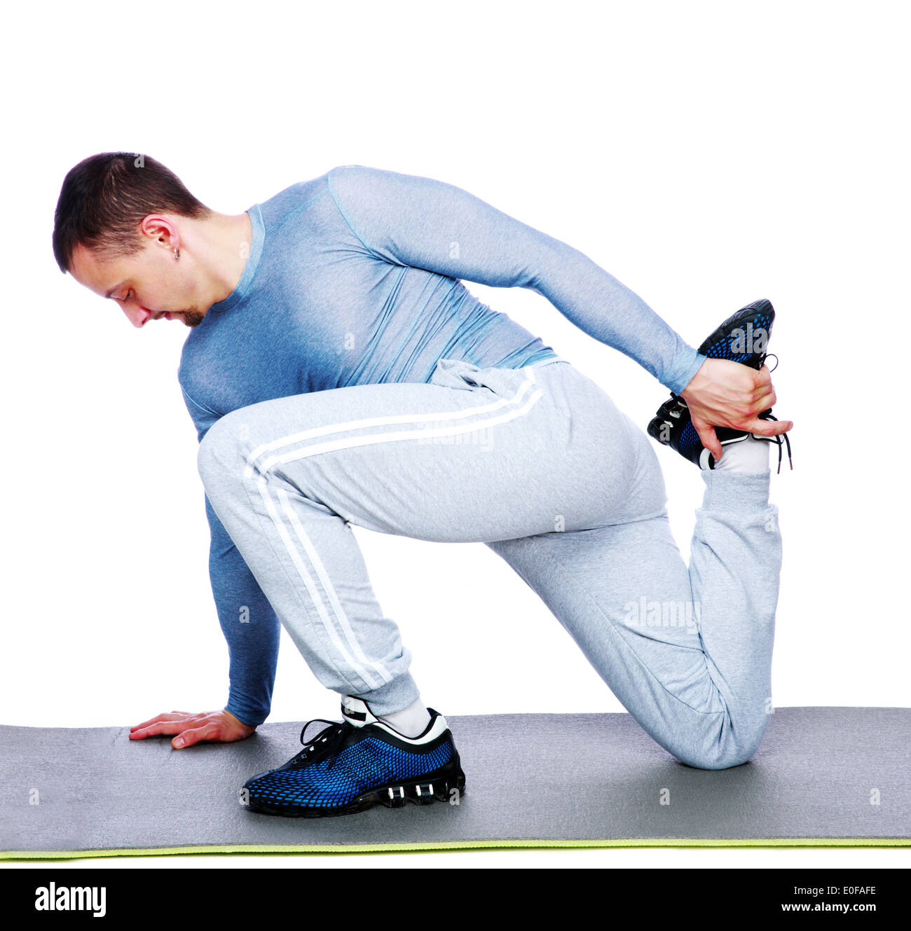 Deportes hombre estirando sobre fondo blanco. Imagen De Stock