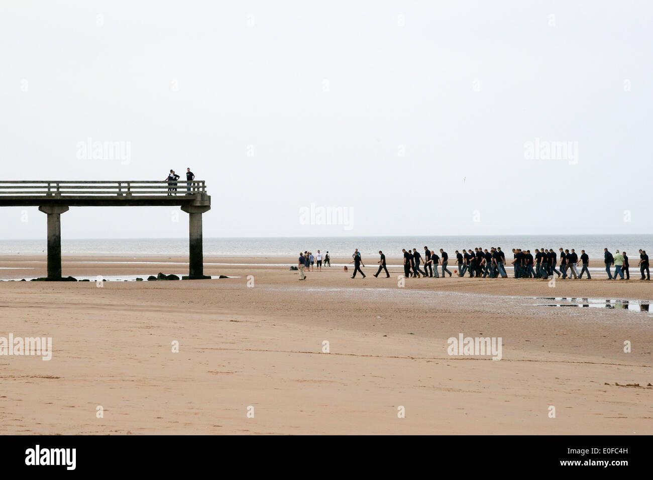 La playa de Omaha, Normandía, Francia. Antiguo muelle en la playa de Omaha en la marea baja. Muestra un grupo del ejército francés caminando cerca del muelle. Foto de stock