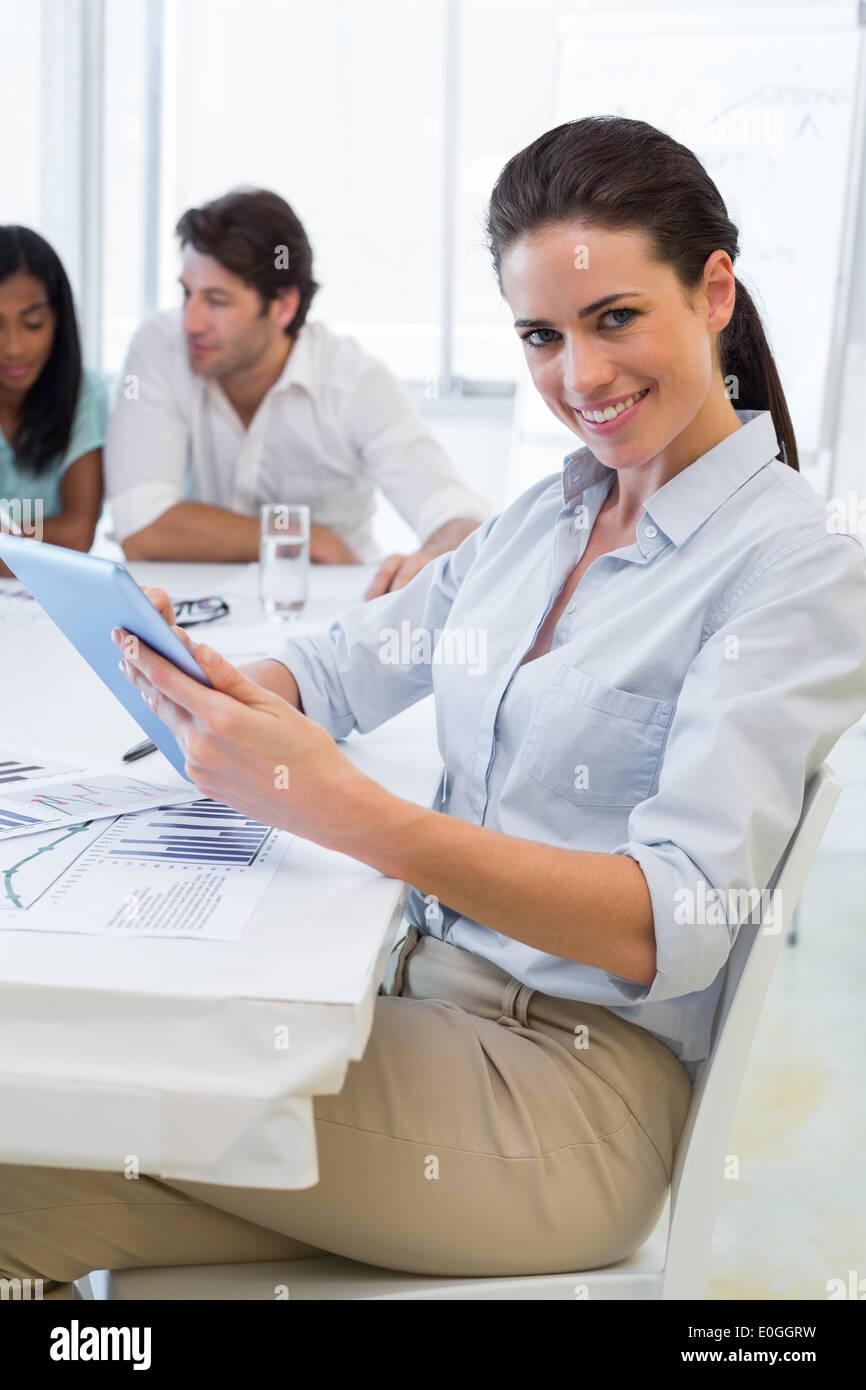 Bastante empresaria mediante dispositivo tablet en reunión de negocios Imagen De Stock