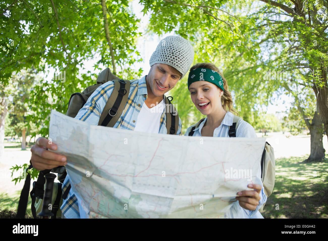 Pareja sonriente activa una caminata consultando el mapa Foto de stock