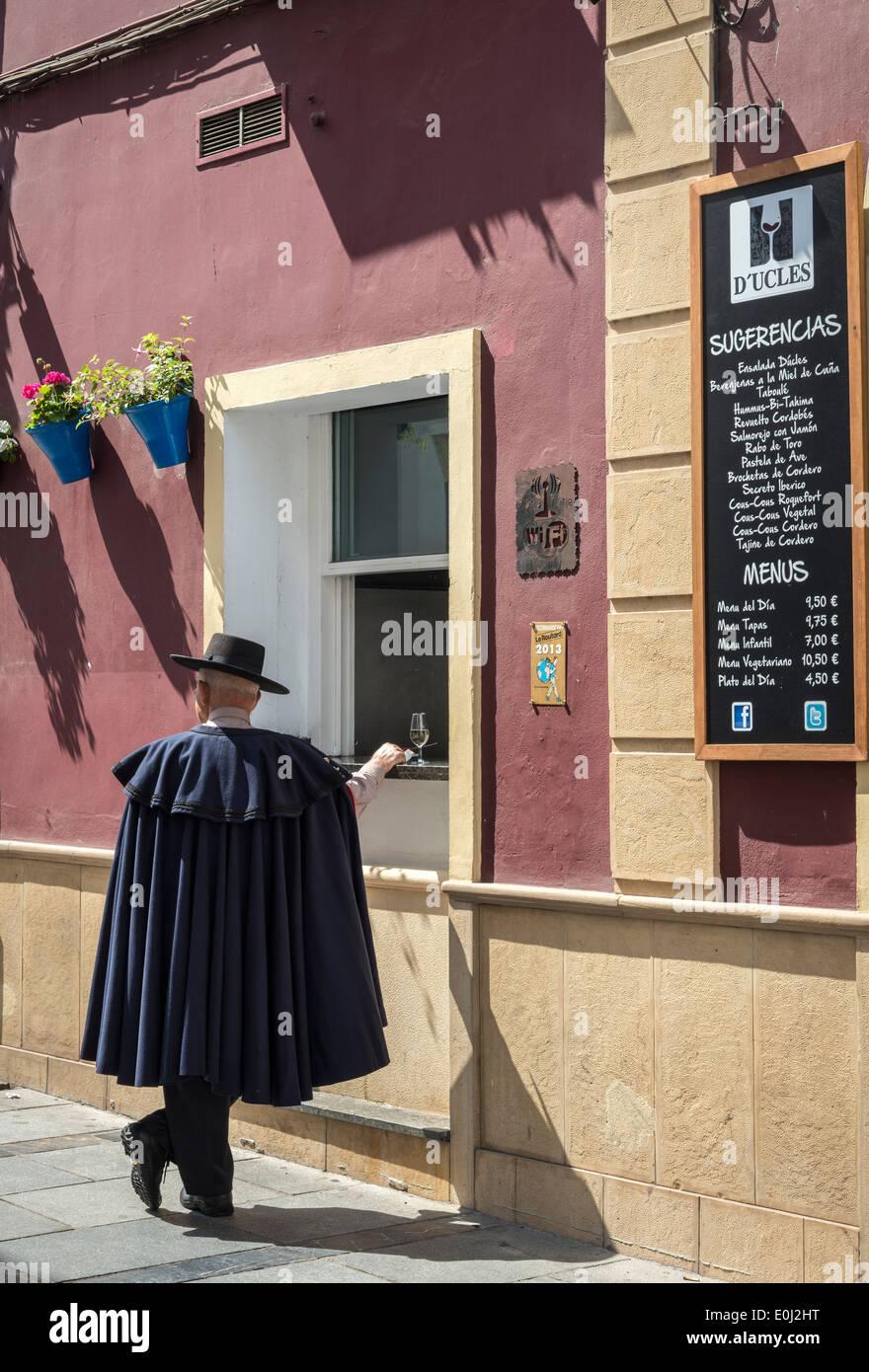 Un hombre en un sombrero tradicional andaluza y manto paradas para tomar una copa en un bar cerca de la Plaza del Foto de stock
