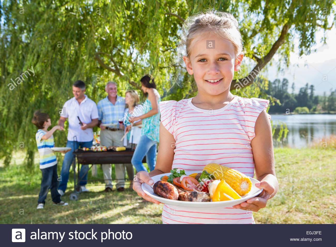 Familia Multi-Generation disfrutando de la Barbacoa por el lago Imagen De Stock