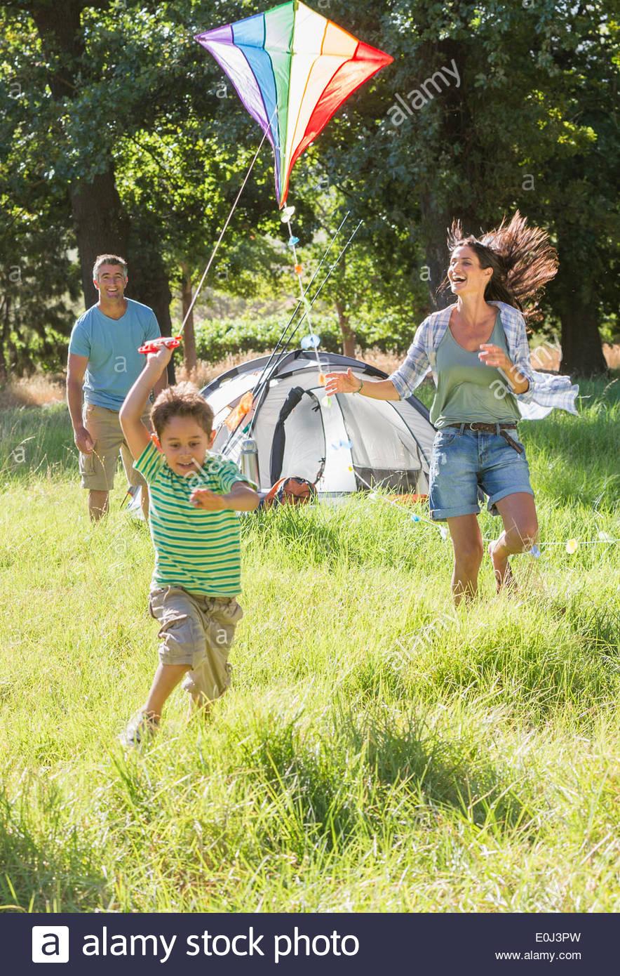 Familia Flying Kite en camping vacaciones en campo Imagen De Stock