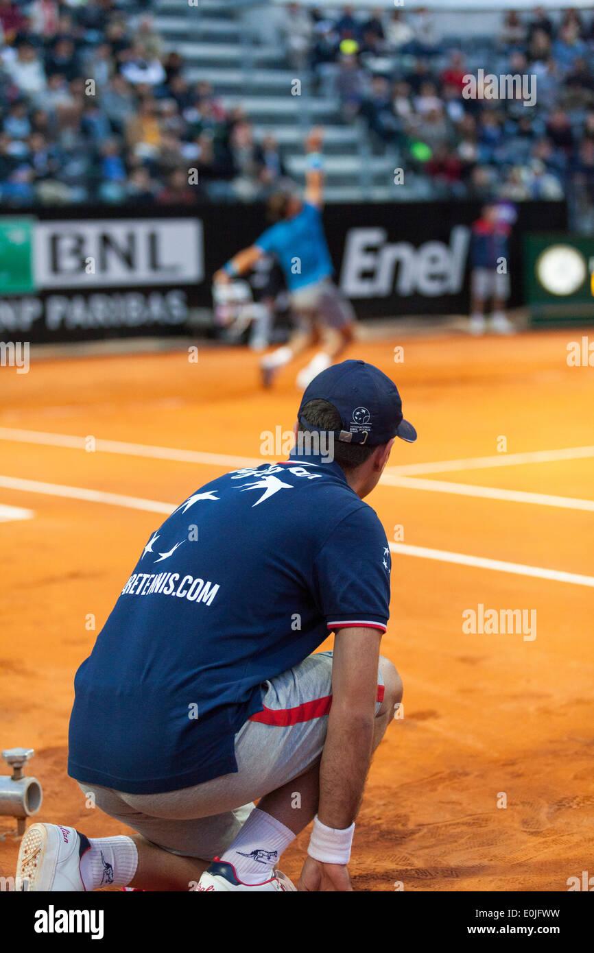 Ball boy en el lado de la corte mientras Rafael Nadal sirve en partido de tenis Foto de stock
