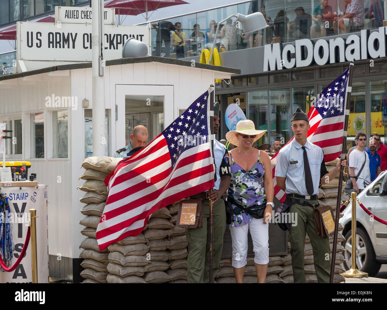 Los turistas posando en el Checkpoint Charlie, en Berlín, Alemania, fue la guerra fría, punto de cruce entre Berlín Oriental y Occidental. Imagen De Stock