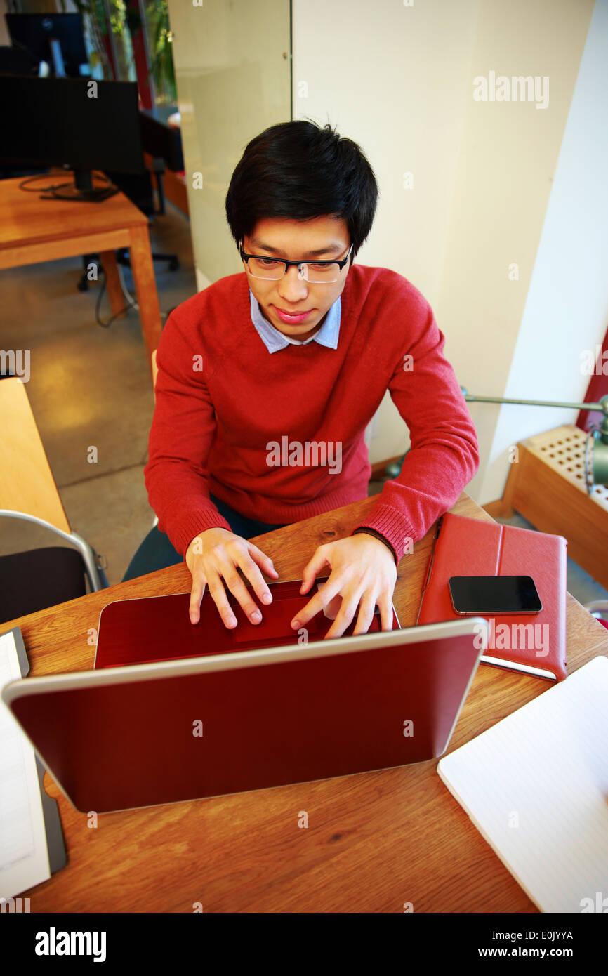 Smart hombre asiático en vidrios trabajando en el portátil en la oficina Foto de stock