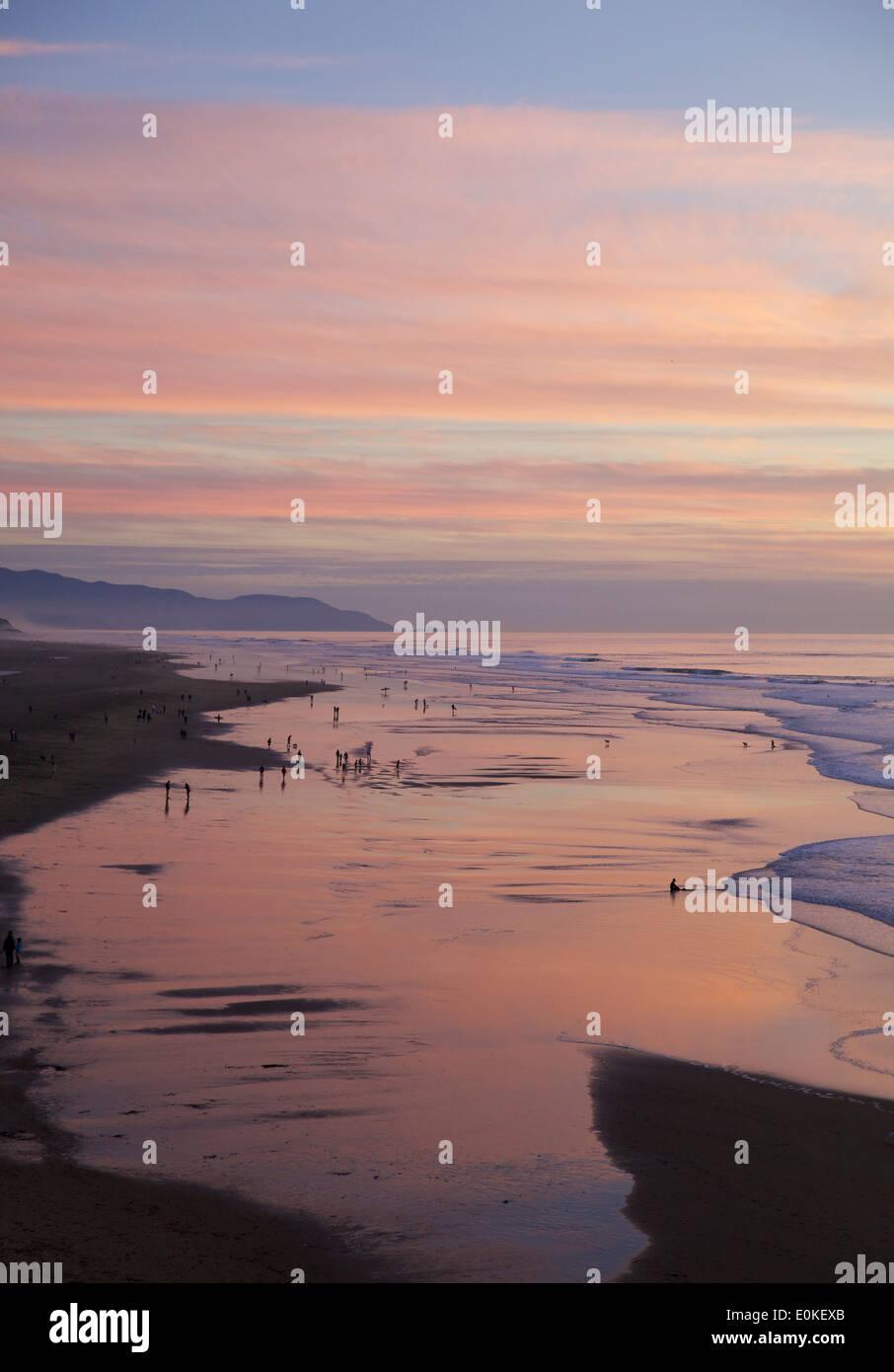 La gente caminando a lo largo de la costa son siluetas contra un brillante atardecer con colores azul, rosa y púrpura y naranja. Imagen De Stock