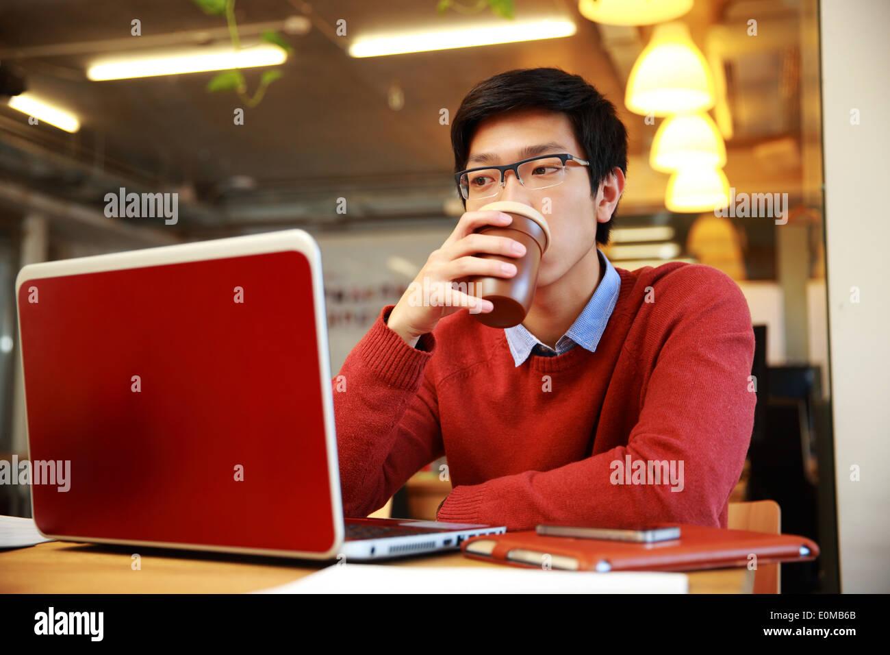 Apuesto hombre asiático trabajando en el portátil y bebiendo café Foto de stock