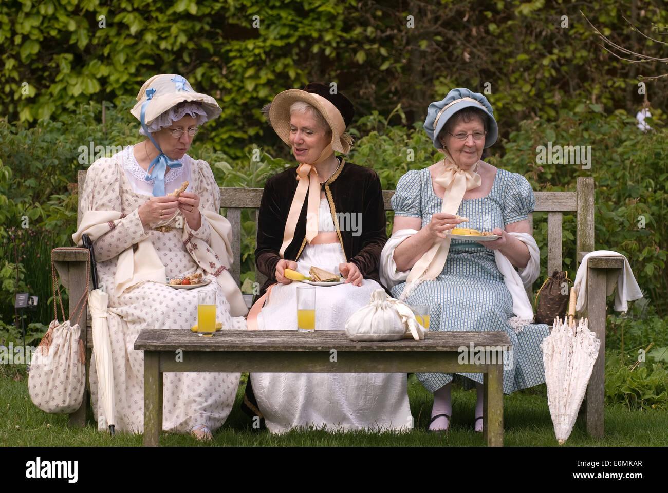 3 mujeres vestidas con el traje de Regency en el jardín de la casa de Jane Austen en Chawton, cerca de Alton, Hampshire, Reino Unido. Imagen De Stock