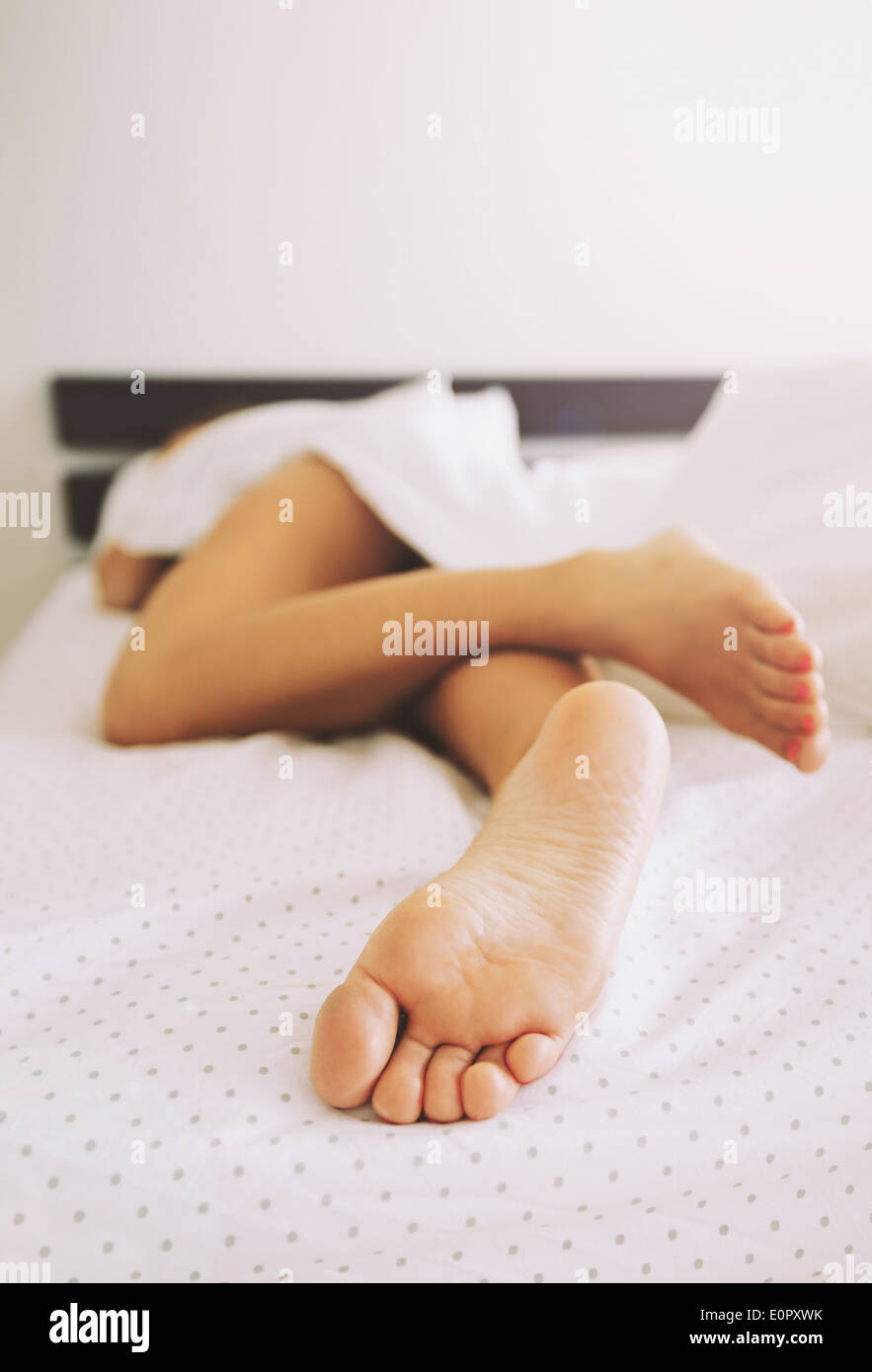 Las piernas desnudas de una mujer joven dormía en su cama, en su casa. Se centran en las piernas. Imagen De Stock
