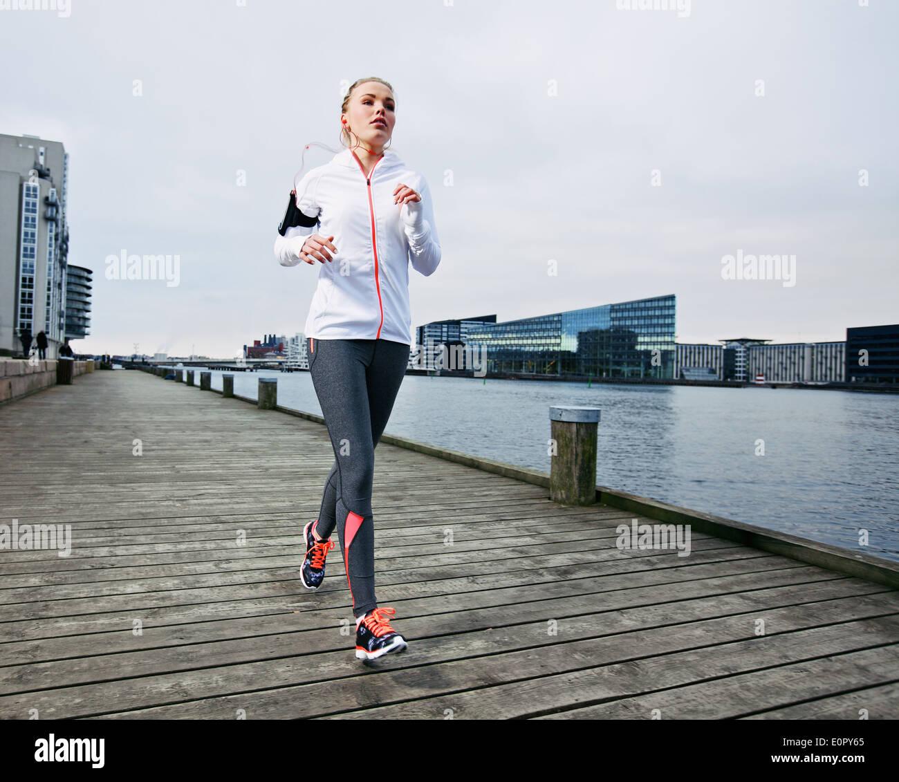 Corredoras formación fuera. La atleta femenina caucásica trotar en el Boardwalk a lo largo de río en la ciudad. Colocar joven que trabaja. Imagen De Stock