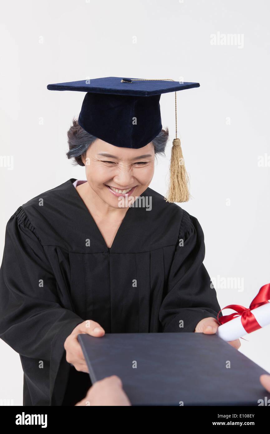 810abdeb2 Una mujer anciana con un atuendo de recibir un diploma de graduación Imagen  De Stock