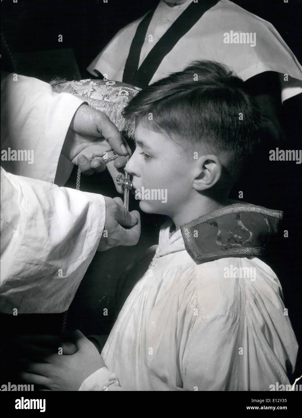 El 26 de febrero de 2012 - un joven obispo: Timothy Owen-Burke besa la cruz celebrada para él por el Rev. Morse-Boycott, durante la ceremonia de su iniciación como joven obispo. Un muchacho se hizo un Obispo durante 23 días: trece-año-viejo Timoteo Owen-Burks fue hecho un muchacho Obispo según la centenaria-custom y ceremonias, en Santa María de la escuela Angel Canción, Addlestone, Surrey, famoso como un internado produciendo coristas conocido como ''Angela'',y dirigido por el reverendo Desmond Morse-Boycott, causando la Premiere Imagen De Stock