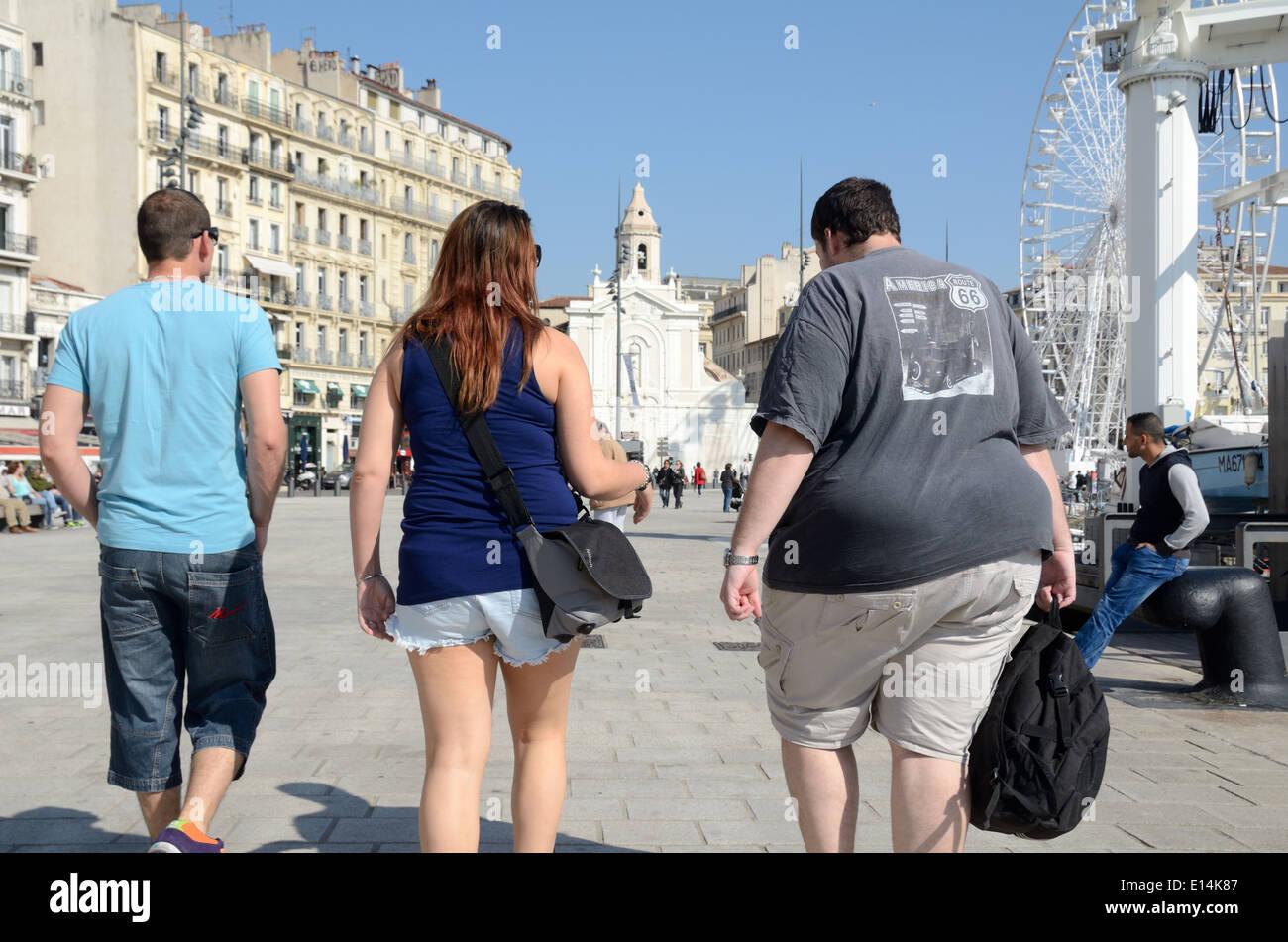 Tres jóvenes, incluidos los grandes obesos Fat Man Walking en Quai du Port Puerto Viejo de Marsella Francia Imagen De Stock