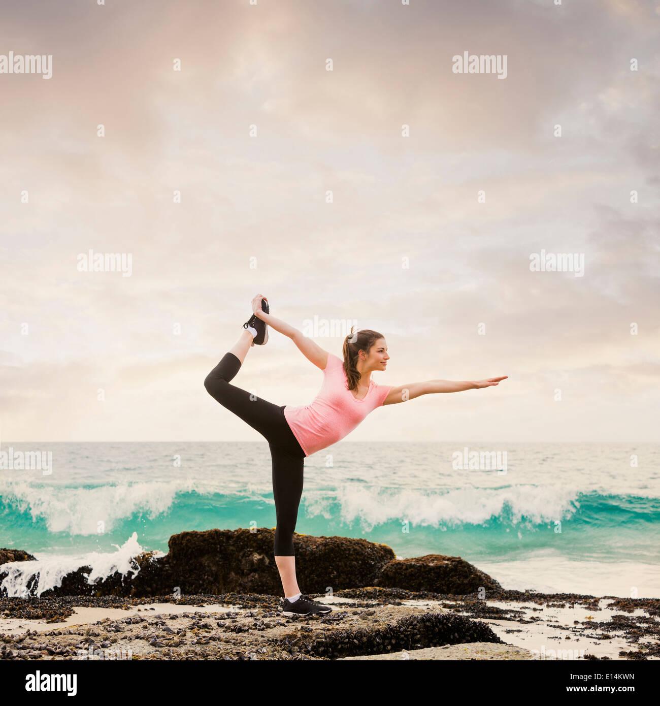 Mujer caucásica estiramiento en la playa Foto de stock