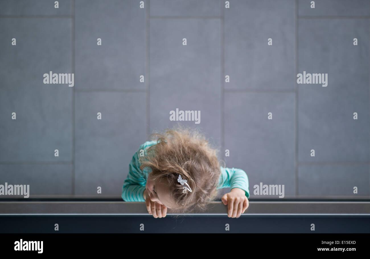 Niña mirando por encima de la baranda, vista desde arriba Imagen De Stock