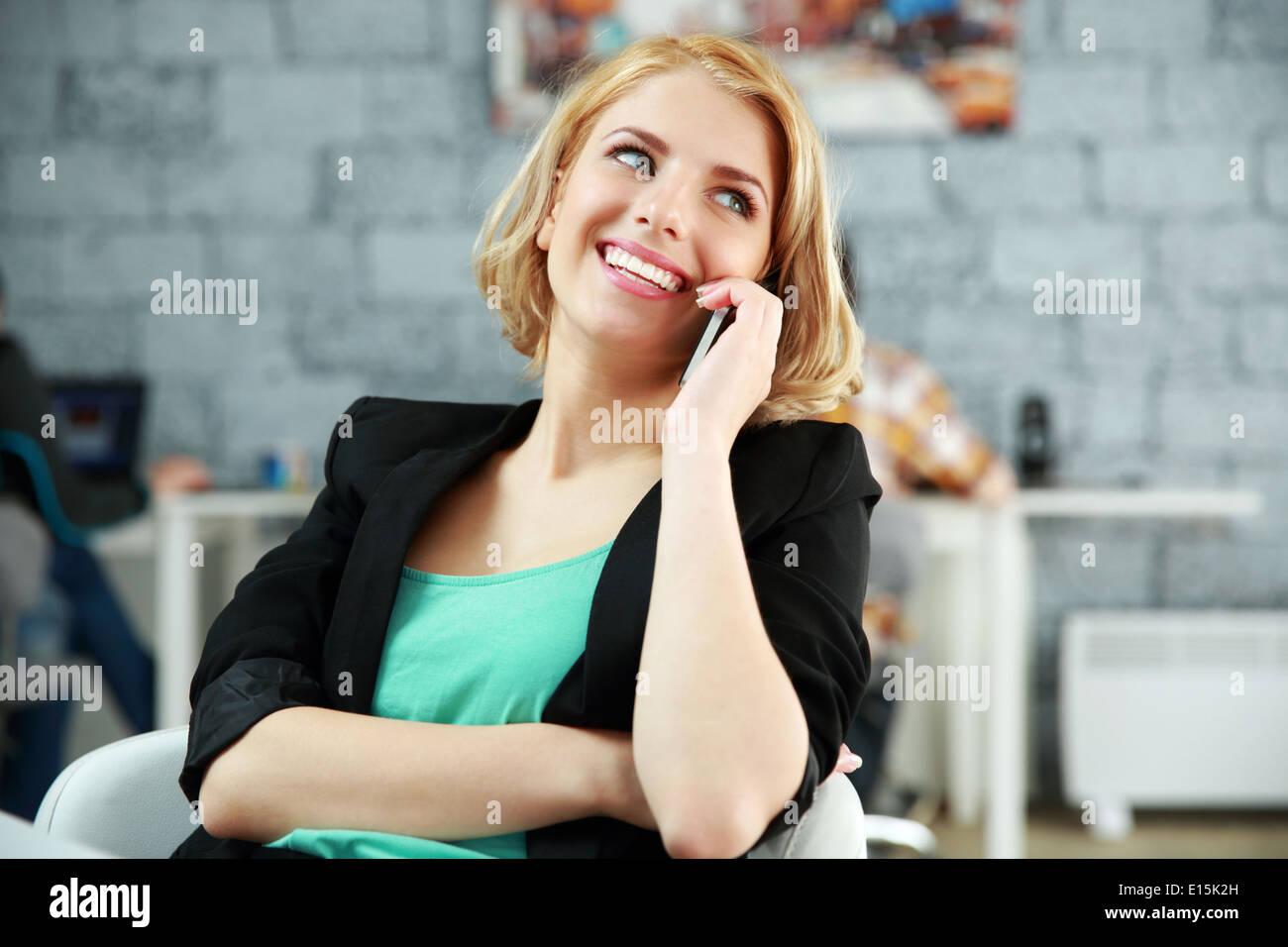 Feliz joven mujer hablando por teléfono en la oficina Foto de stock