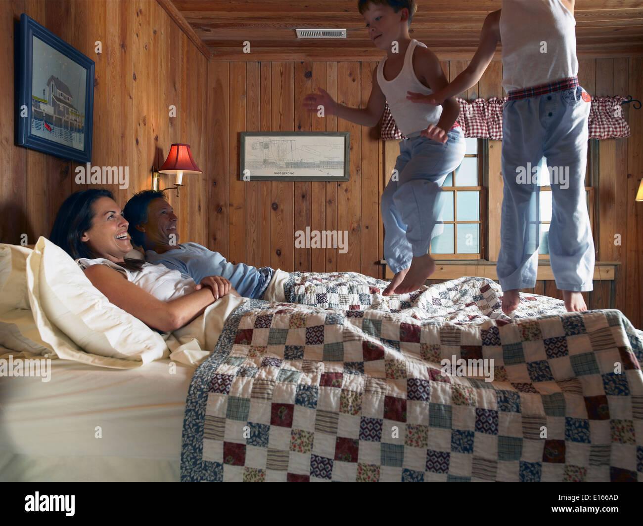 Los muchachos saltar en la cama de los padres. Foto de stock