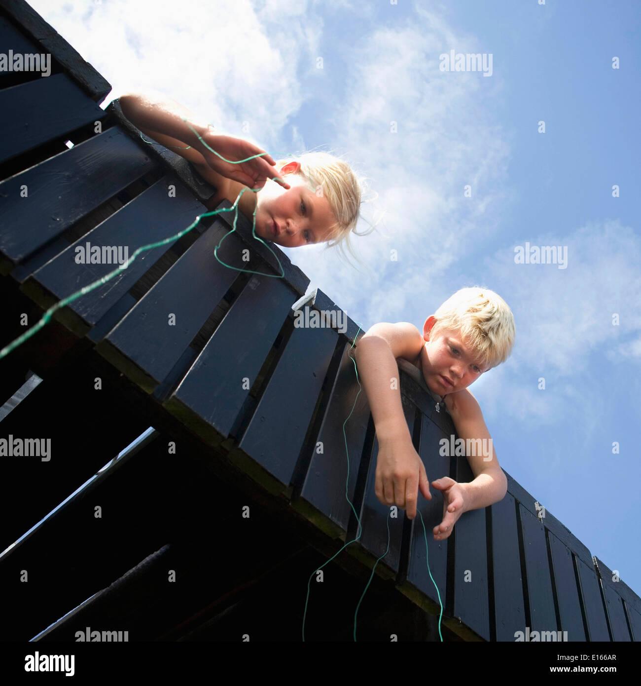 Dos niños de pesca desde el puente mediante cadena Foto de stock