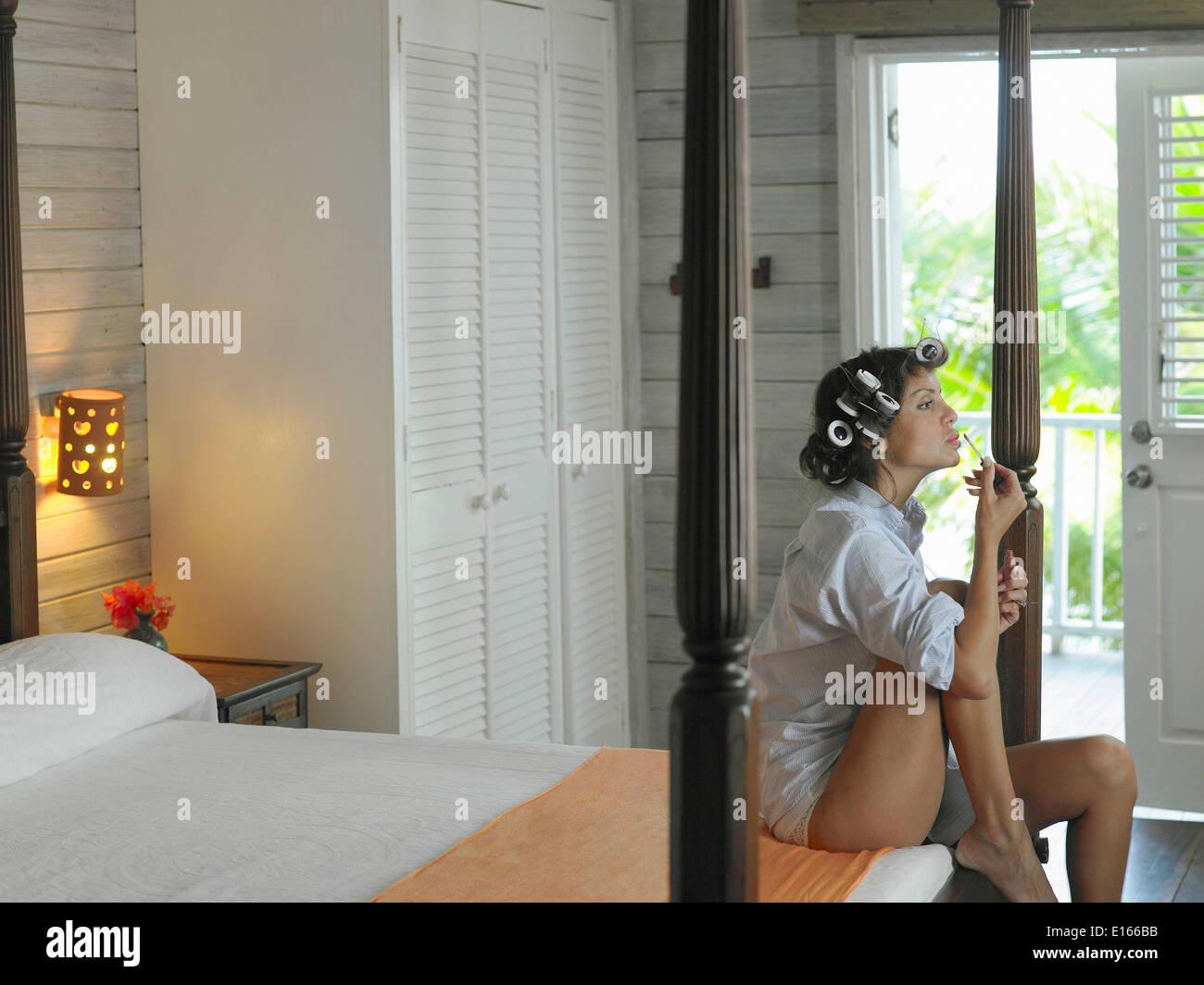 Latino mujer sentada en la cama aplico maquillaje Foto de stock