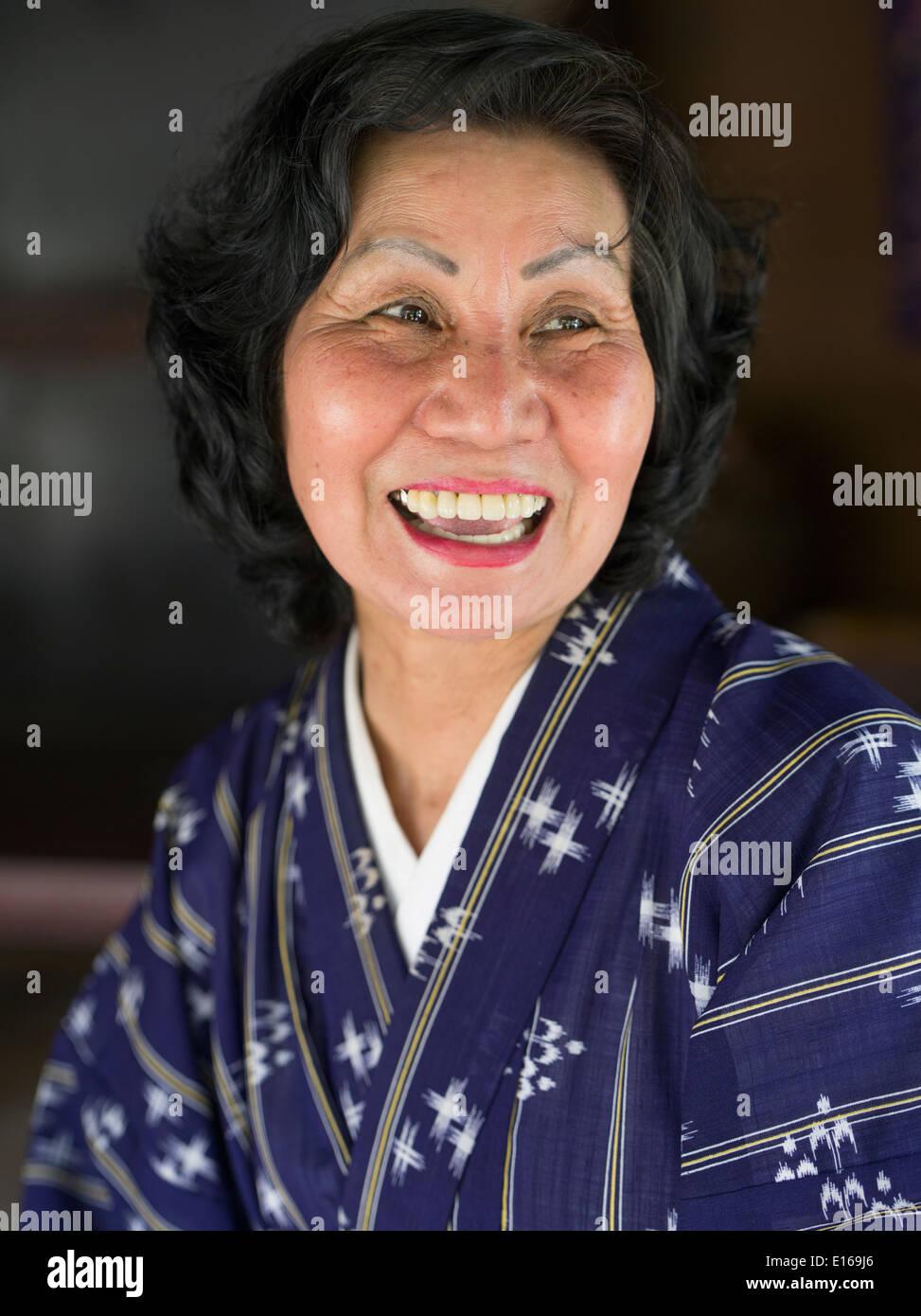 Hermosa mujer vistiendo yukuata ancianos de Okinawa y sonriente. Mura Ryukyu, Okinawa, Japón Imagen De Stock