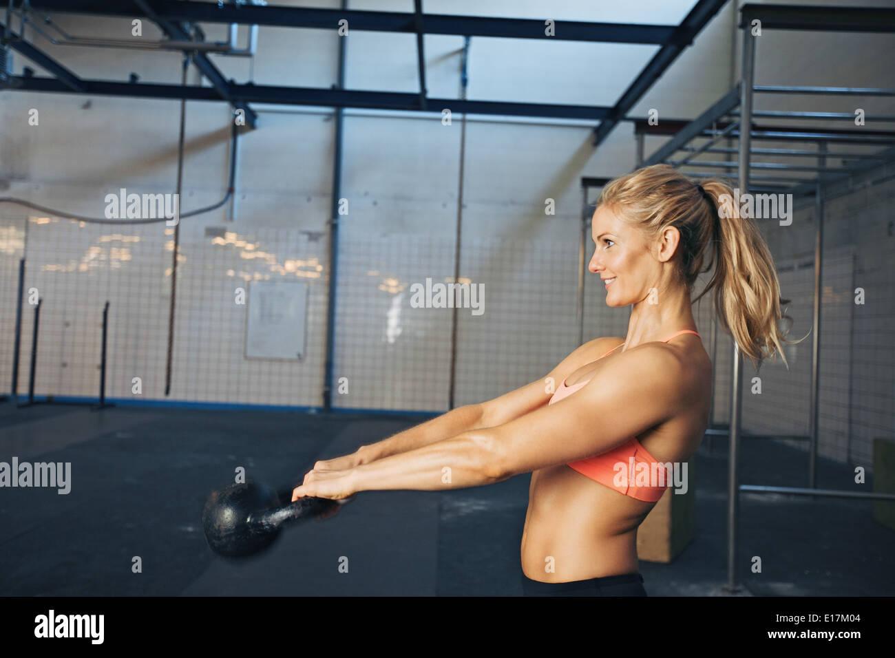Vista lateral del joven feliz ejerciendo con hervidor bell al gimnasio. La atleta femenina crossfit caucásica haciendo ejercicio en el gimnasio. Imagen De Stock