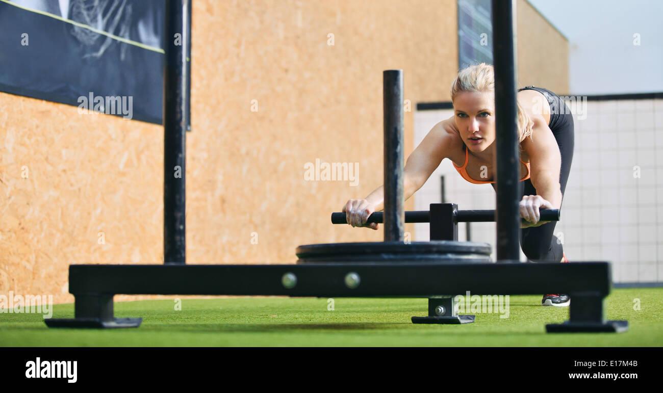 Musculoso y fuerte hembra joven empujando el prowler equipamiento de ejercicio sobre el césped de hierba artificial. Colocar mujer haciendo ejercicio. Imagen De Stock