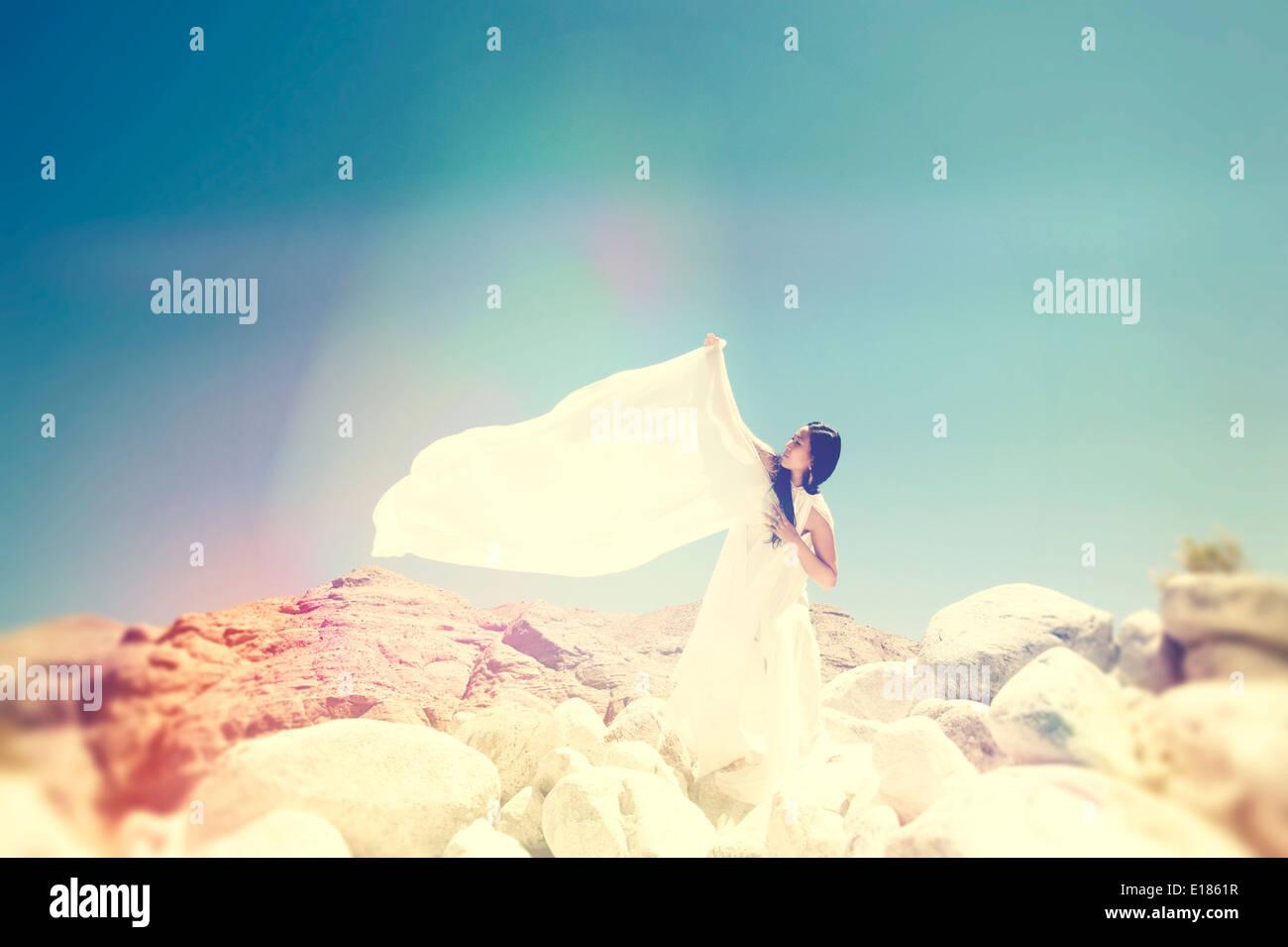 Mujer de blanco en la cima de una montaña. Imagen De Stock