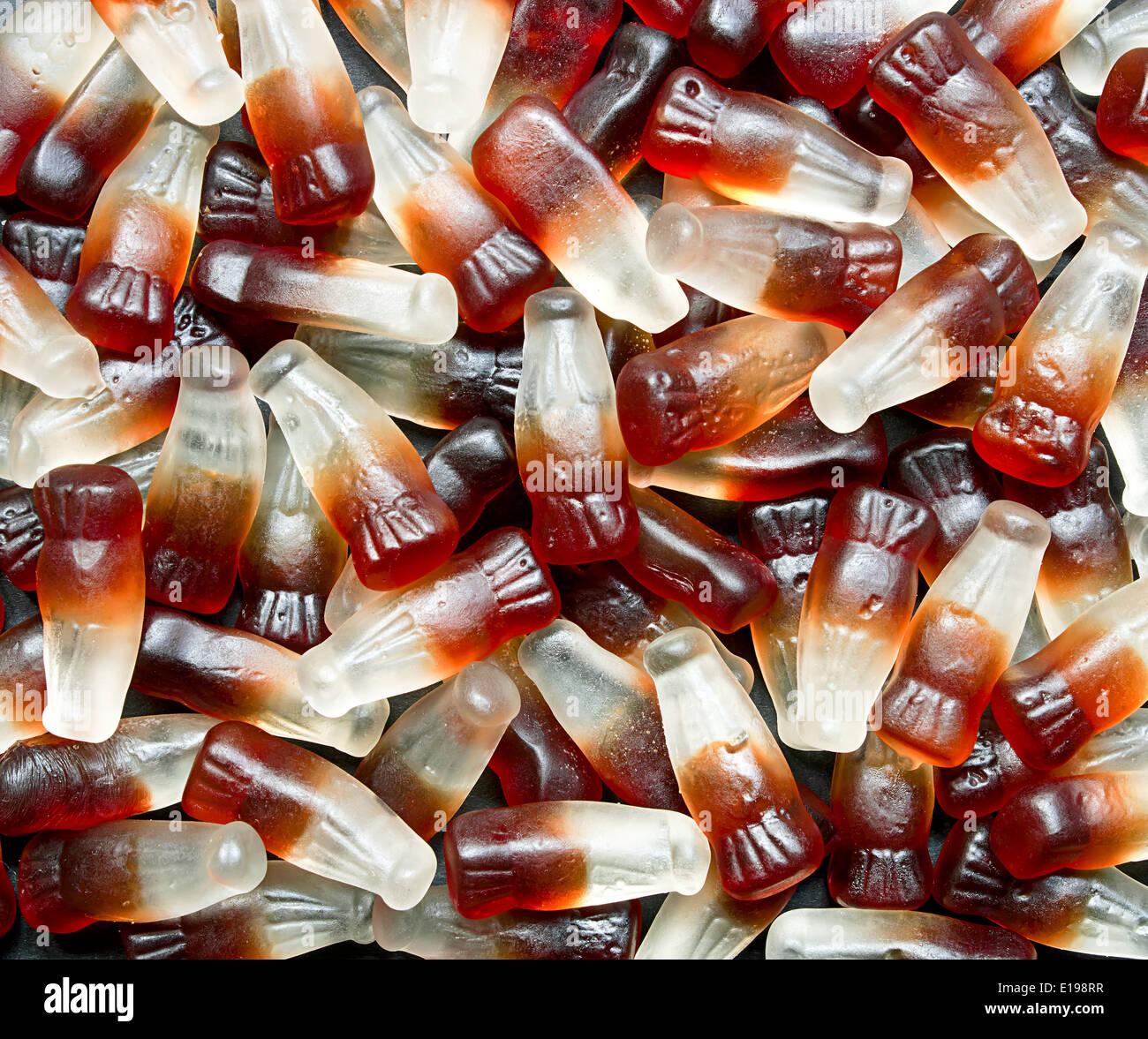 Gomosas cola botella al fondo un dulce retro popular también conocido como caramelos blandos en un pick and mix en el mercado de autoservicio. Imagen De Stock