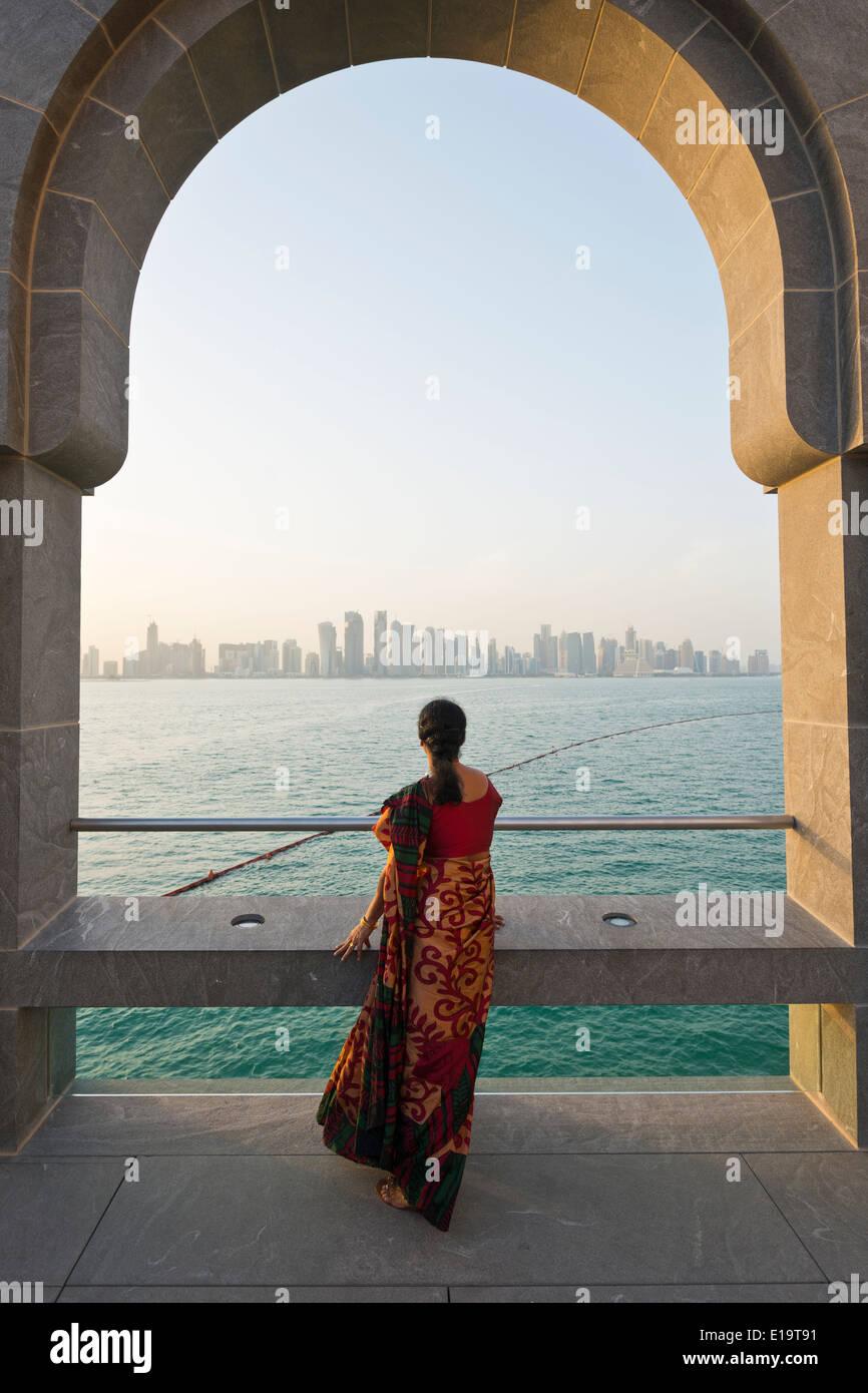 Doha. Qatar. Vistitor mirando a través de la Bahía de Doha desde el Museo de Arte Islámico. Imagen De Stock