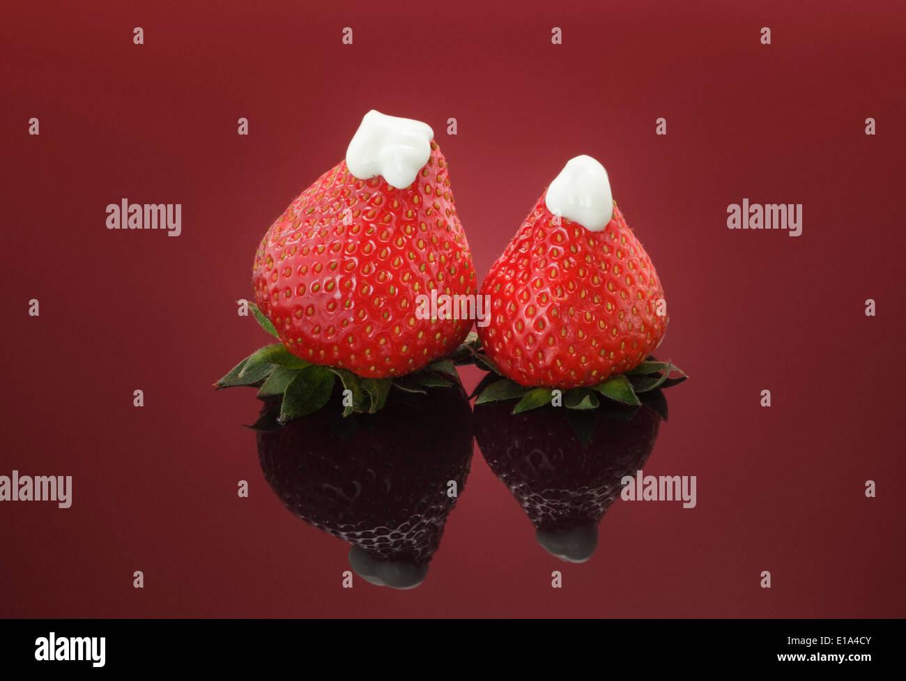 Dos fresas frescas rematado con gruesos yogur natural sobre fondo rojo. Imagen De Stock