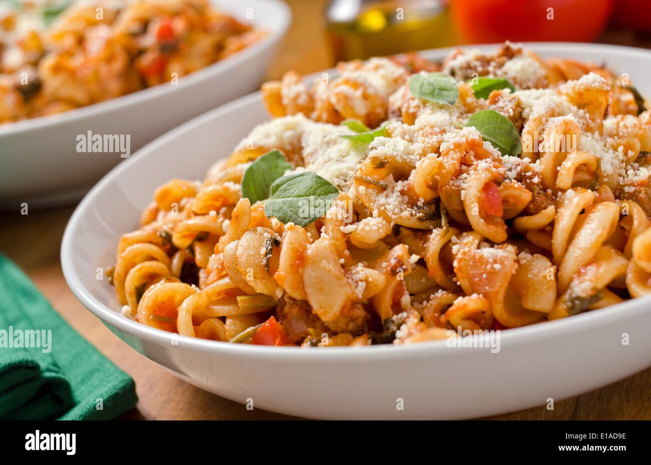 Rotini pasta con salsa marinara, queso parmesano y albahaca fresca. Imagen De Stock